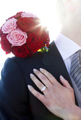 Bröllopsbukett och vigselring på hand