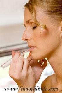 Makeupartist målar läpparna på den blivande bruden.